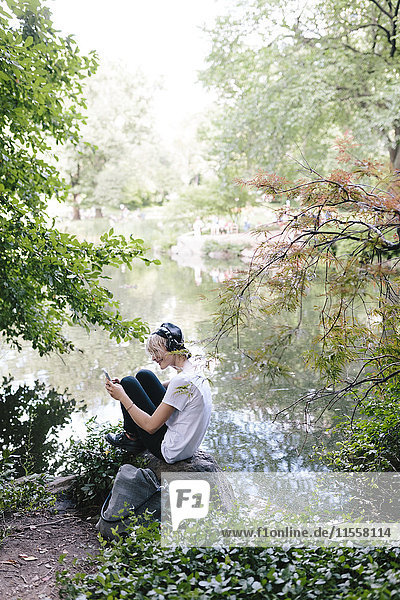 Junge Frau am Seeufer im Park mit Kopfhörer und Blick aufs Handy
