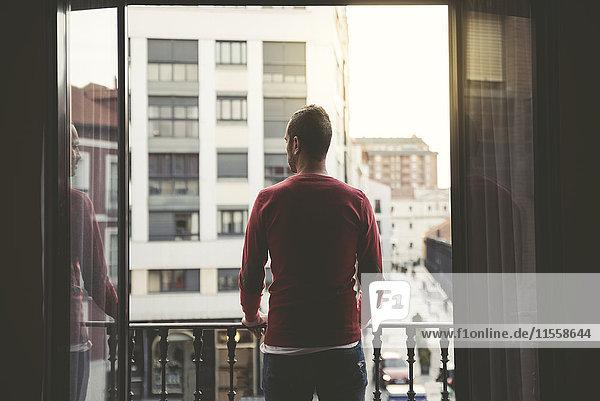 Mann auf einem Balkon in der Stadt bei Sonnenuntergang Mann auf einem Balkon in der Stadt bei Sonnenuntergang