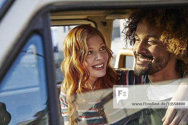 Lächelnde junge Frau schaut Freund im Auto an