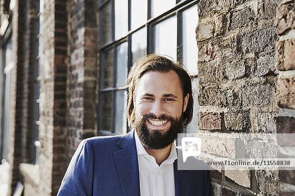 Porträt eines glücklichen Geschäftsmannes außerhalb des Backsteinbaus