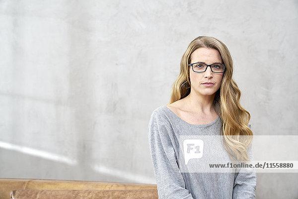 Porträt einer ernsthaften blonden Frau mit Brille