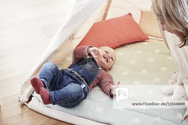 Glückliches kleines Mädchen  das auf der Decke liegt und Großmutter ansieht.