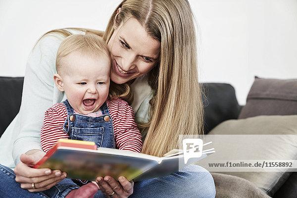 Mutter und glückliches kleines Mädchen zu Hause beim Betrachten des Buches