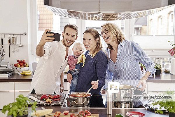 Fröhliches Familienkochen in der Küche mit einem Selfie