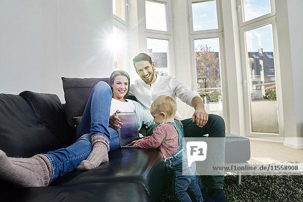 Eltern mit Baby Girl mit Laptop auf der Couch