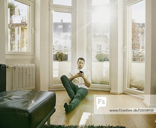 Mann sitzt auf dem Boden und schaut auf das Handy.