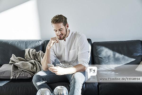Lächelnder Mann sitzt auf der Couch und schaut aufs Handy.