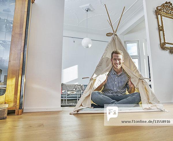 Lächelnder Mann im Tipi auf dem Boden sitzend