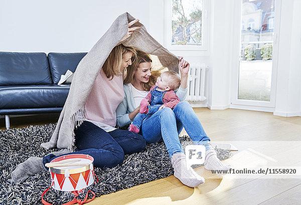 Großmutter  Mutter und kleines Mädchen beim Spielen im Wohnzimmer