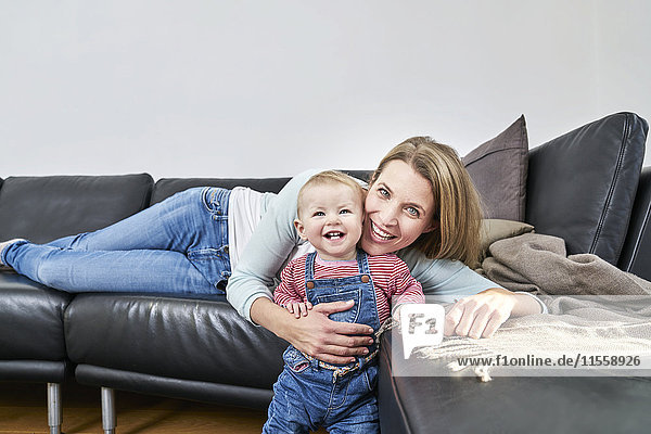 Glückliche Mutter und kleines Mädchen zu Hause auf der Couch