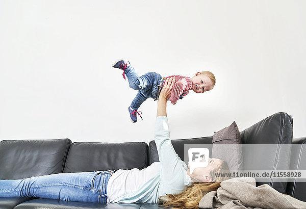 Glückliche Mutter hebt das Mädchen auf der Couch hoch.