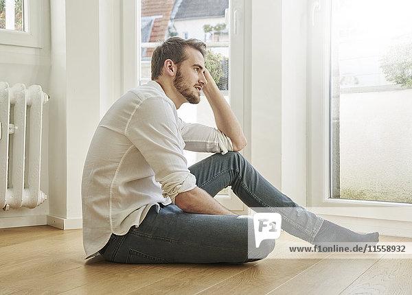 Mann auf dem Boden sitzend