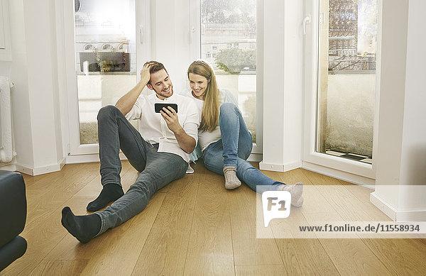 Lächelndes Paar sitzt auf dem Boden und schaut auf das Handy.