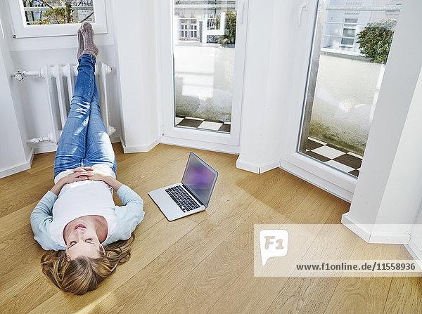Frau zu Hause auf dem Boden neben dem Laptop liegend