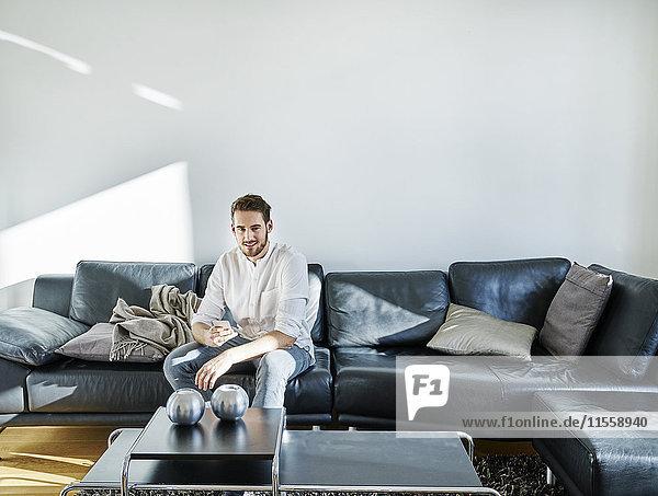 Lächelnder Mann sitzt auf der Couch und hält sein Handy.