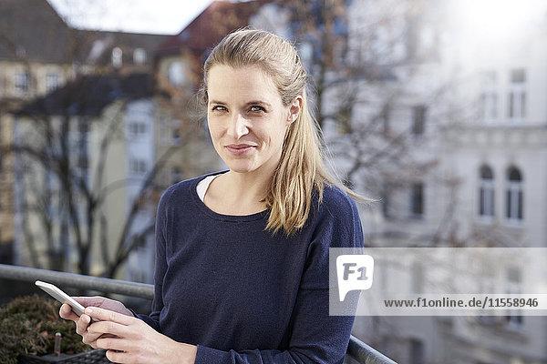 Porträt einer lächelnden Frau mit Handy auf dem Balkon