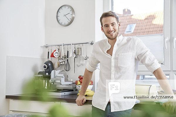Porträt eines lächelnden jungen Mannes in der Küche