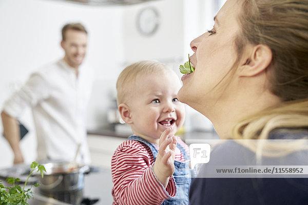 Mutter mit Mädchen in der Küche beim Kräuteressen