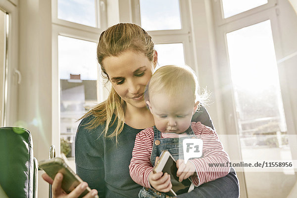 Mutter und kleines Mädchen mit Mobiltelefonen