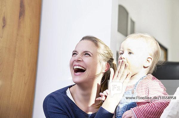 Glückliche Mutter mit dem kleinen Mädchen zu Hause