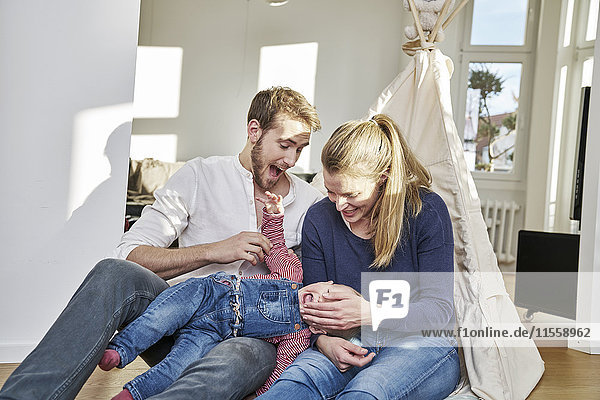 Glückliche Familie mit einem kleinen Mädchen  das zu Hause spielt.