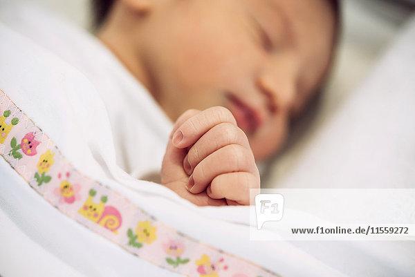 Neugeborenes Mädchen schläft unter einer Decke mit Blumenmuster