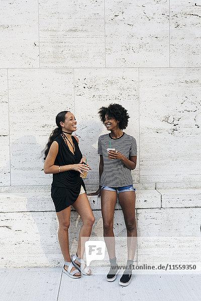 Zwei lachende Freunde mit Getränken  die vor einer Wand stehen.