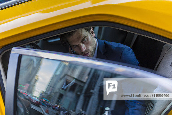 Businessman sitting in taxi  using smart phone