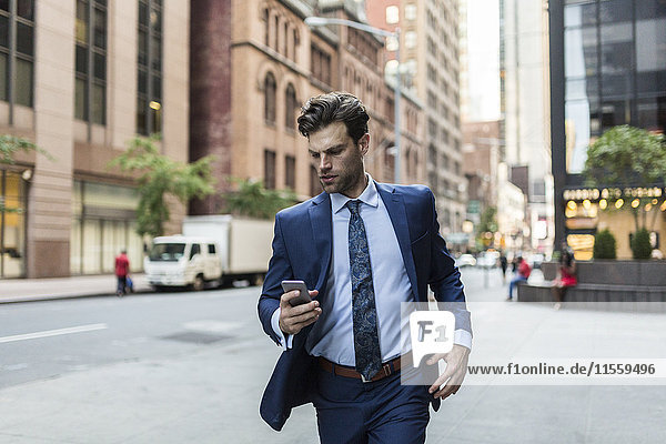 Handsone businessman in a hurry running through Manhattan  using smart phone