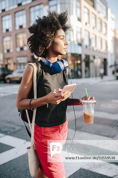 Junge Frau mit Kopfhörer und Smartphone Crossong Street in Brooklyn  carying take away drink