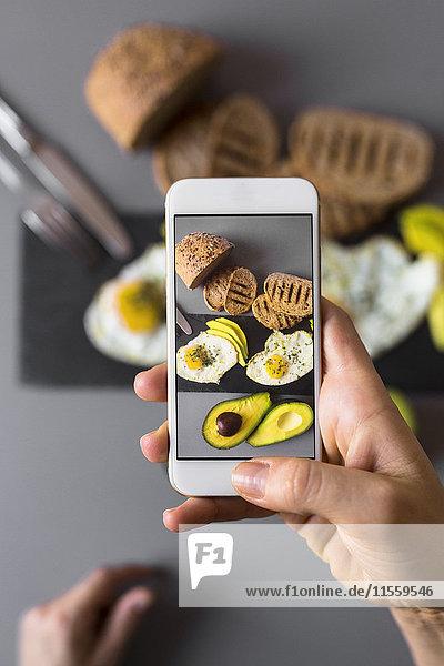 Handaufnahme eines Smartphone Fotos vom Frühstück mit Avocados und Eiern