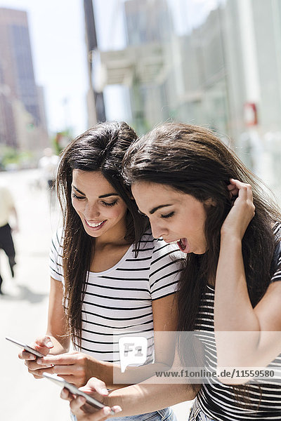 USA  New York City  two happy twin sisters looking at cell phones in Manhattan