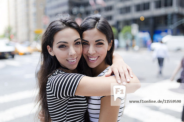 USA  New York City  portrait of two beautiful twin sisters in Manhattan hugging