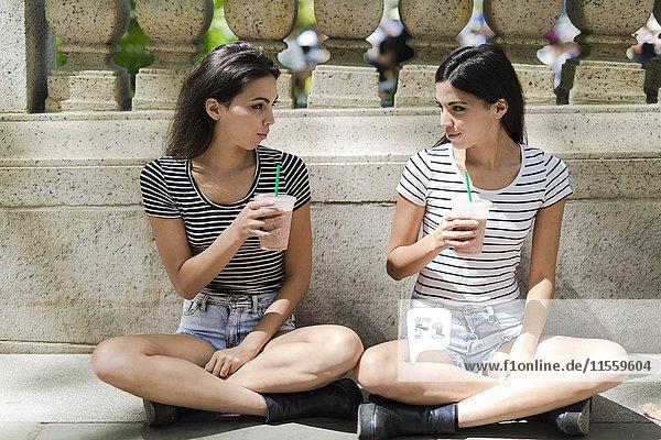 Zwei Zwillingsschwestern sitzen im Freien und trinken etwas zum Mitnehmen.