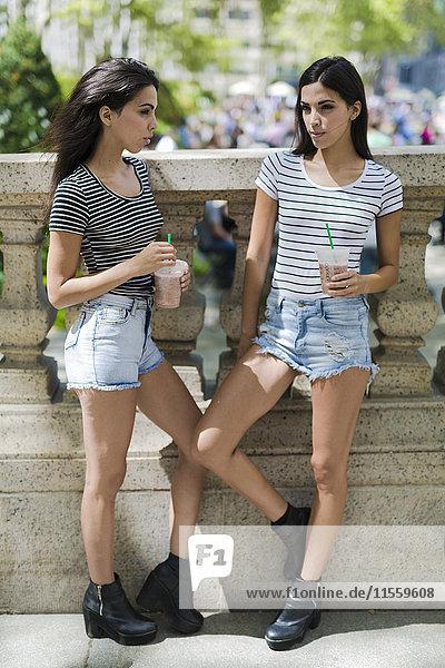 Zwei Zwillingsschwestern im Freien bei einem Getränk zum Mitnehmen