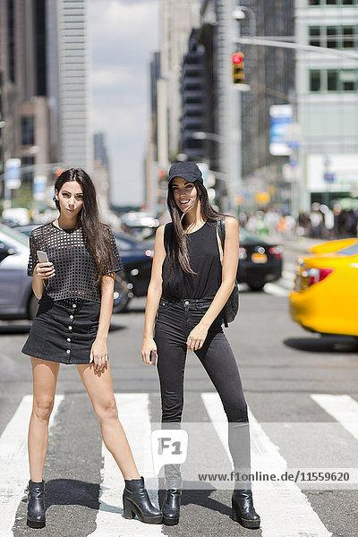 USA  New York City  zwei modische Zwillingsschwestern auf Zebrastreifen in Manhattan