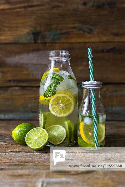 Glasflaschen mit aufgegossenem Wasser mit Zitrone  Limette  Minzeblättern und Eiswürfeln Glasflaschen mit aufgegossenem Wasser mit Zitrone, Limette, Minzeblättern und Eiswürfeln