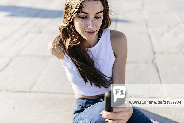 Junge Frau entspannt an der Strandpromenade mit Blick aufs Handy