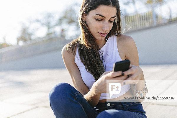 Junge Frau entspannt sich an der Strandpromenade SMS
