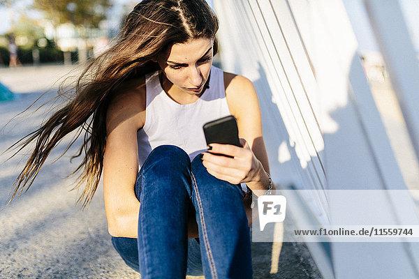 Junge Frau beim Anblick des Handys bei Sonnenuntergang