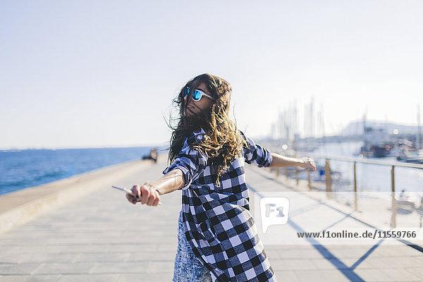 Junge hübsche Frau in Strandkleidung,  die am Meer wackelt