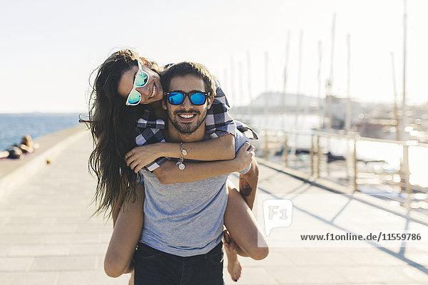 Glückliches Paar am Hafen  Mann mit wman Huckepack