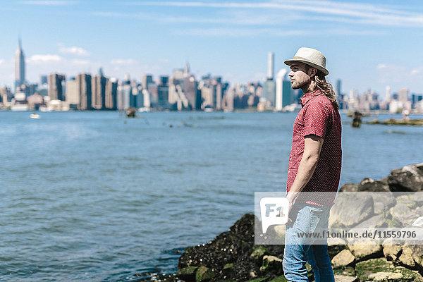 USA  New York City  Mann mit Hut am Wasser mit Skyline von Manhattan im Hintergrund