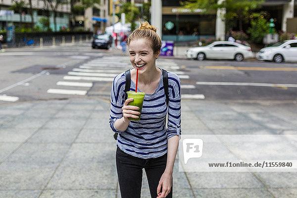 USA  New York City  lachende junge Frau mit einem Smoothie in Manhattan