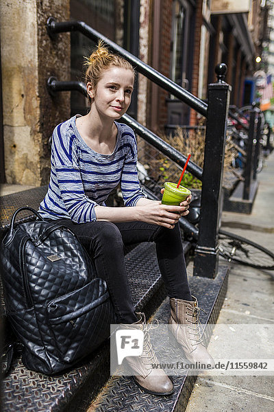 USA  New York City  woman sitting on stoop drinking a smoothie in Manhattan