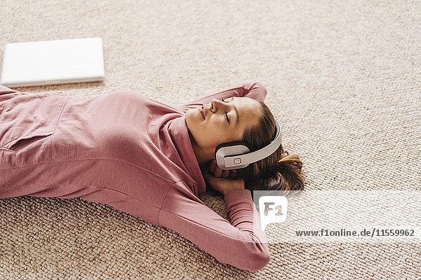 Frau auf dem Teppich liegend mit Kopfhörer