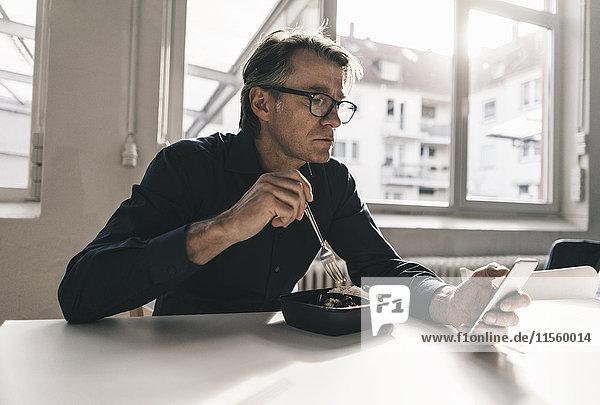 Erwachsener Geschäftsmann beim Telefonieren in der Mittagspause im Büro