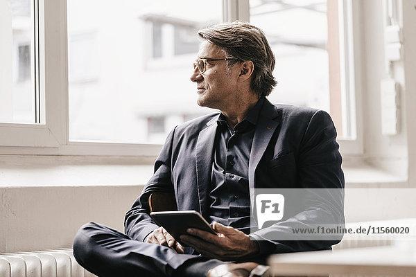 Ein reifer Geschäftsmann  der aus dem Fenster schaut.