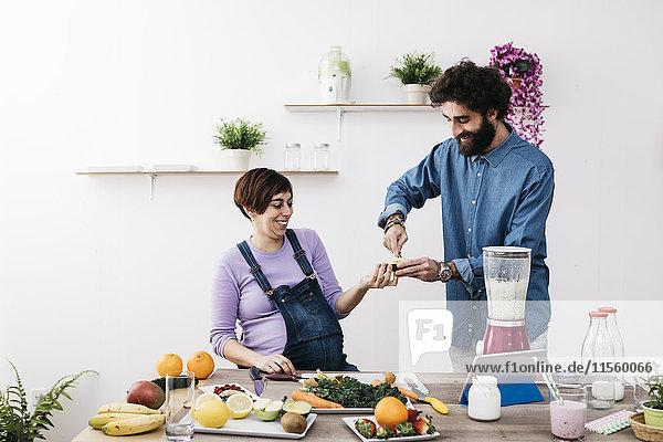 Lächelndes Paar  das gesunde Smoothies mit frischem Obst und Gemüse zubereitet.