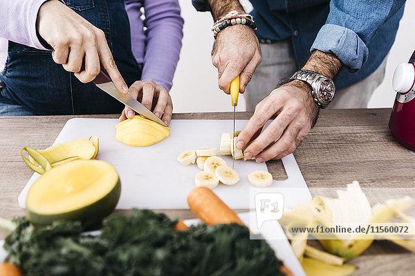 Hände von Paaren  die Früchte für die Zubereitung von Smoothies hacken.
